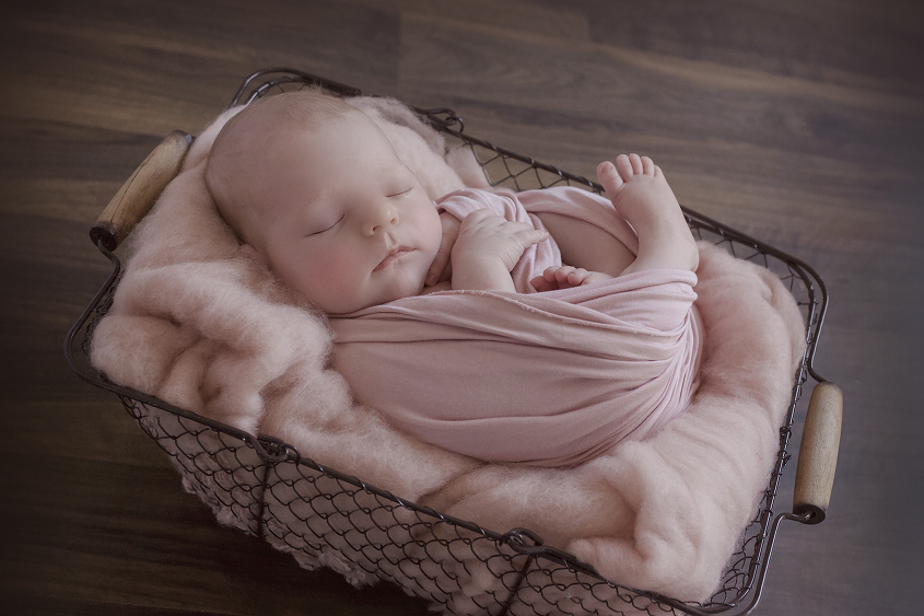 Newborn baby girl sleeping in farmers basket with pink felt and pink wrap on wooden floor