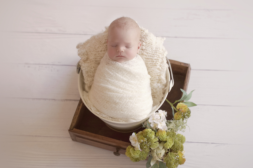 Newborn baby girl wrapped in cream blanket with cream knit layer in bucket sitting in wooden drawer with flowers on white wooden floor