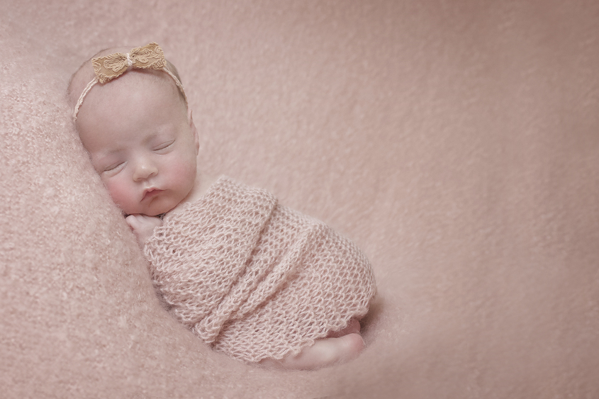 Newborn baby girl sleeping on pink blanket with pink knit layer and bow tieback