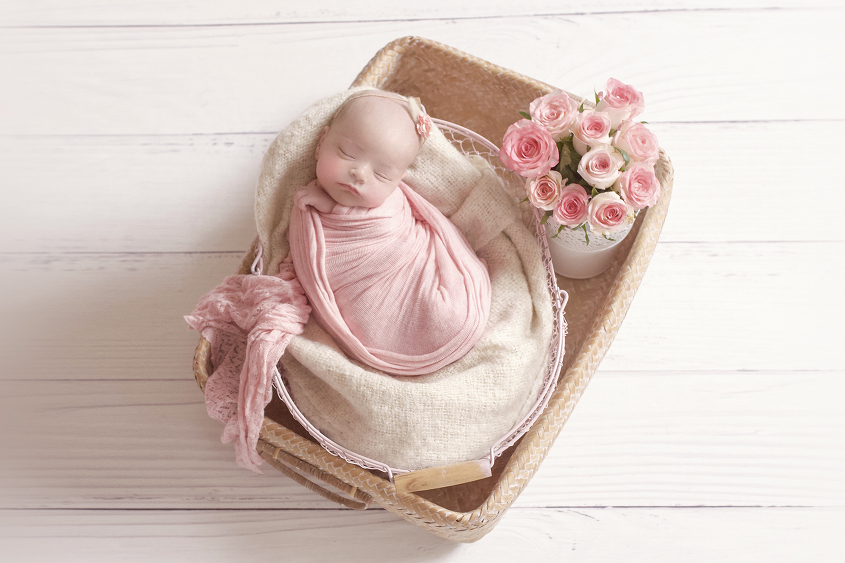 Newborn baby girl wrapped in pink wrap in cane basket with pink farmers basket and cream blanket and bunch of pink roses on white wooden floor