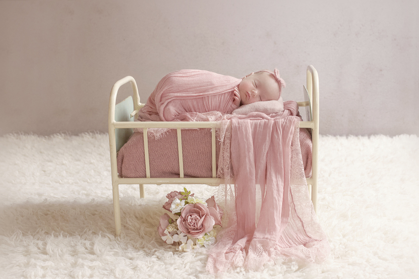 Newborn baby girl sleeping in cream iron bed with pink wraps and blanket and flowers and tieback on cream fur