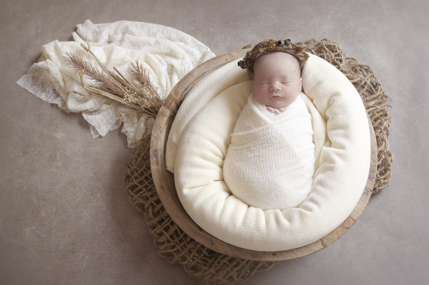 Newborn baby girl sleeping in round wooden bowl with cream blanket and wrap and lace layer with jute layer and dried flowers and baby wearing gumnit tieback