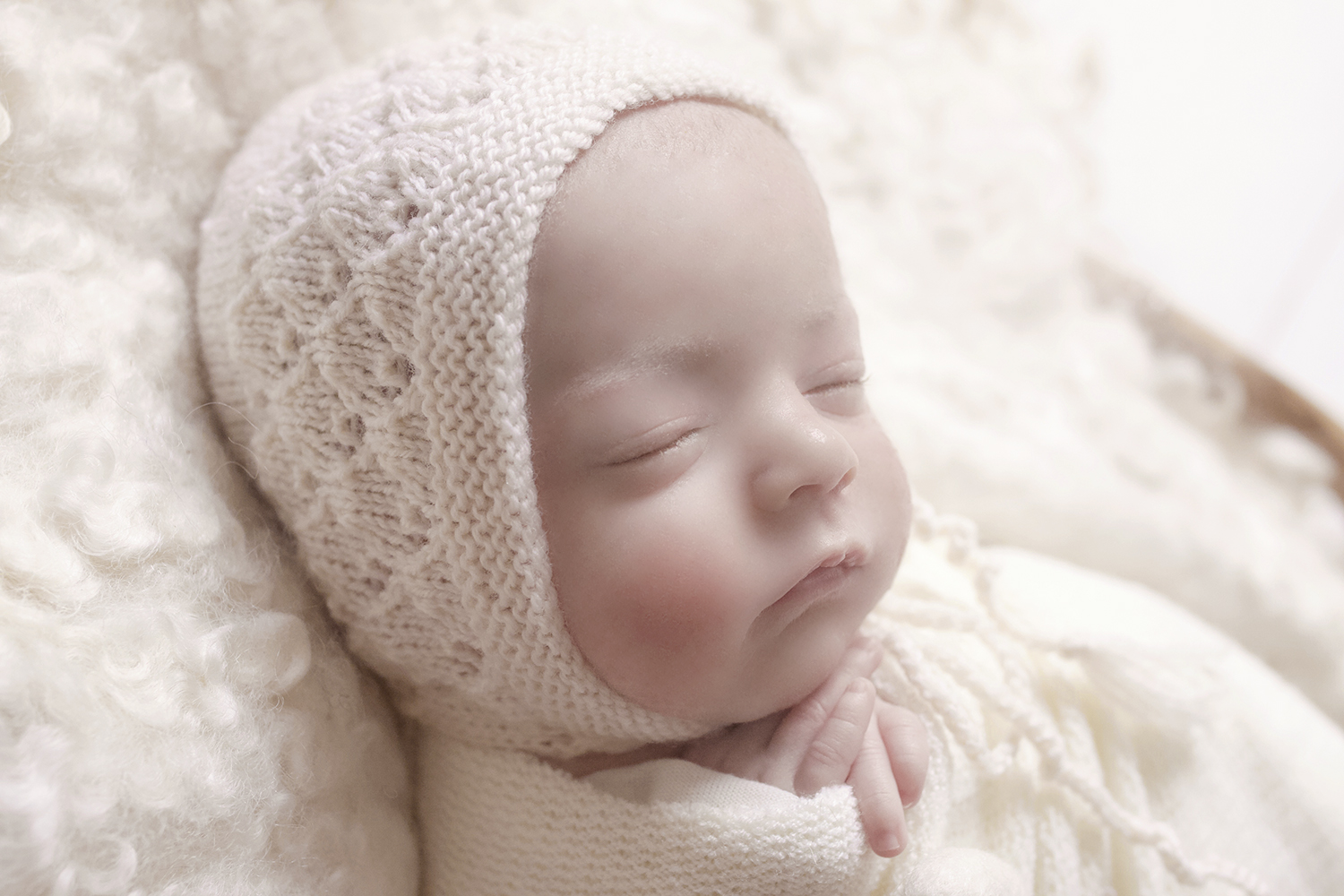Newborn baby girl sleeping in cane basket with cream knit layer and cream wrap and cream felt hearts and tieback on white wooden floor with cream knit bonnet