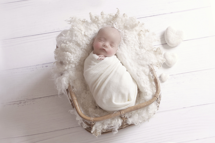 Newborn baby girl sleeping in cane basket with cream knit layer and cream wrap and cream felt hearts and tieback on white wooden floor
