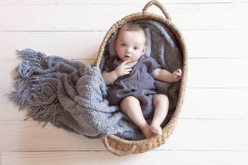 Baby boy sleeping in cane basket wearing blue romper with blue blanket and pillow on white wooden floor