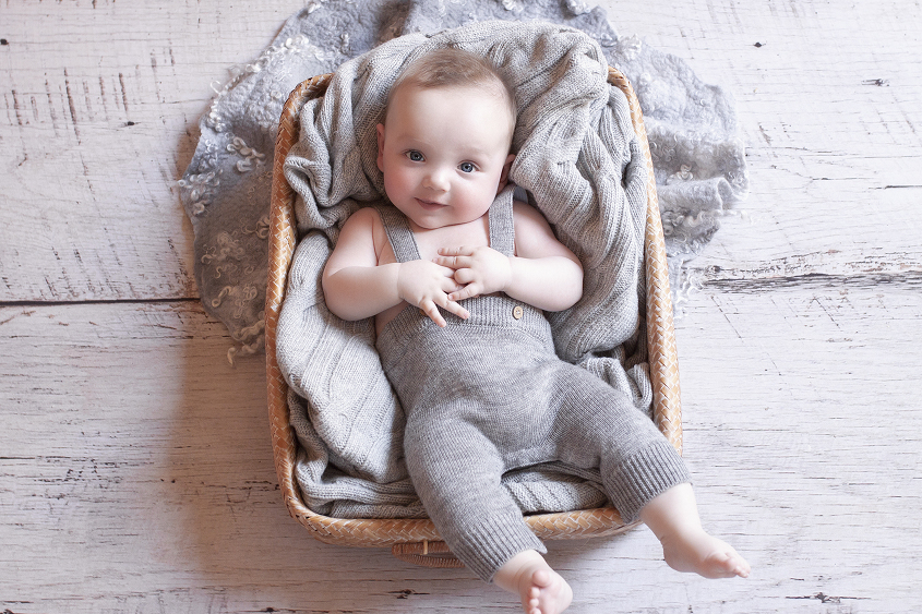 Baby boy in cane basket wearing grey romper with grey blanket and curly felt on white wooden floor