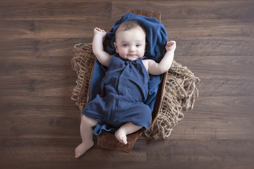 Baby boy in blue romper in wooden trencher with jute layer and blue blanket on wooden floor