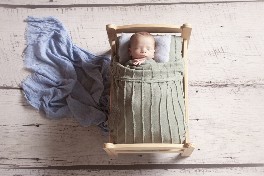 Newborn baby boy sleeping in wooden bed with green blanket and blue wrap and pillow on white wooden floor