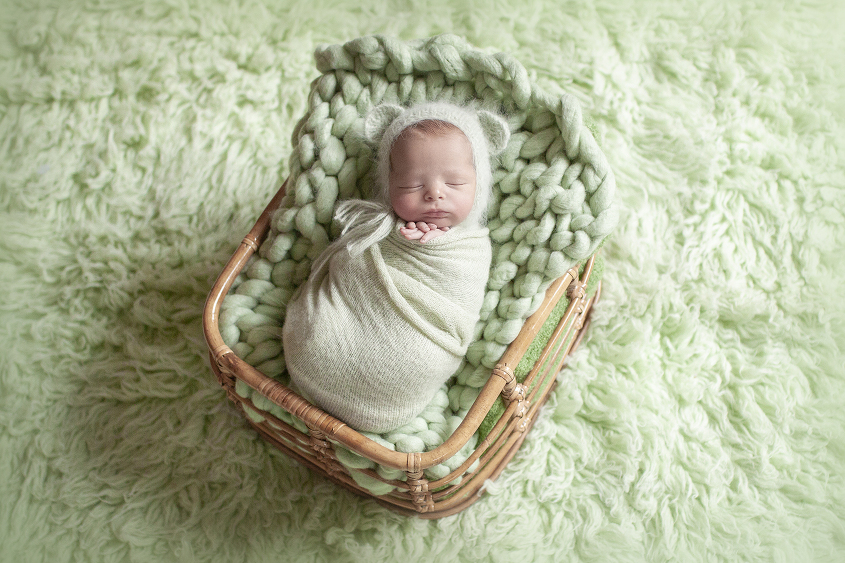 Newborn baby boy sleeping in cane basket with green knit layer and wrap and bear bonnet on green fur