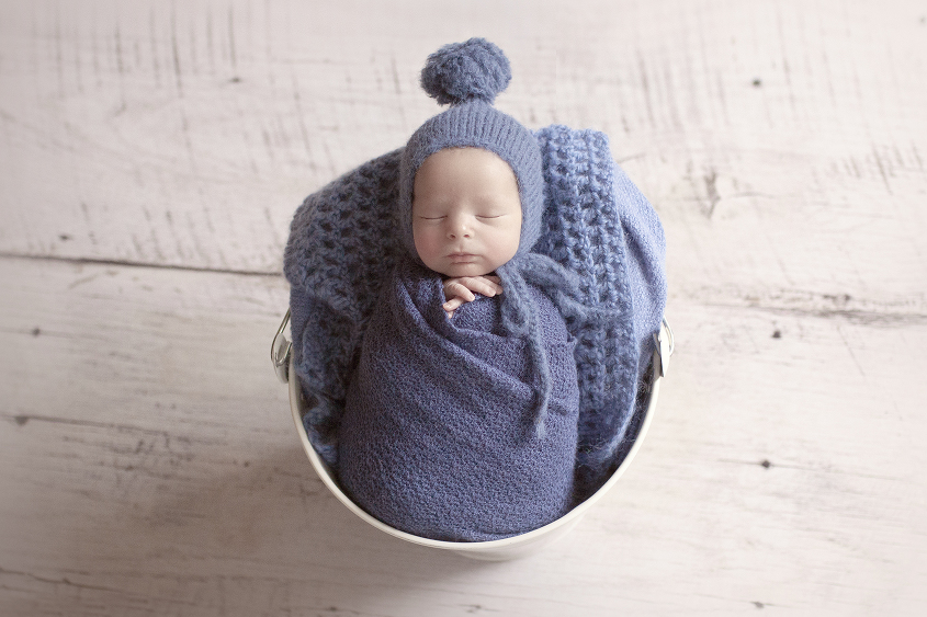 Newborn baby boy sleeping in cream bucket with blue wrap and blanket and bonnet on white wooden floor