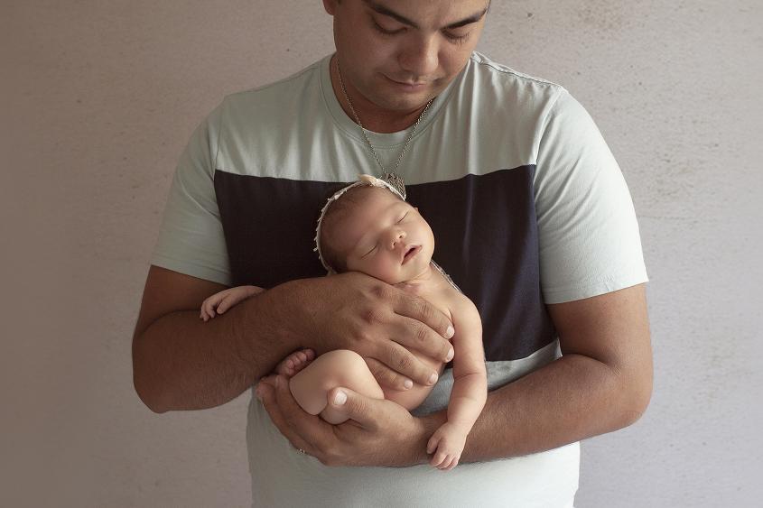 Newborn baby girl sleeping in papas arms