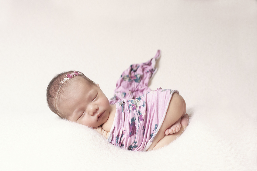 Newborn baby girl sleeping on cream blanket with purple floral wrap and bow tieback