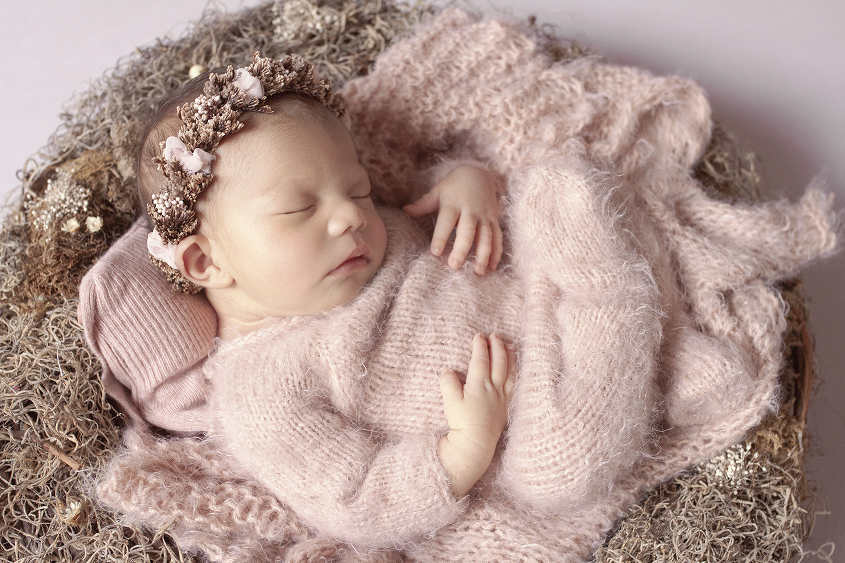 Newborn baby girl sleeping in nest with flowers wearing pink mohair romper and matching wrap with flower halo