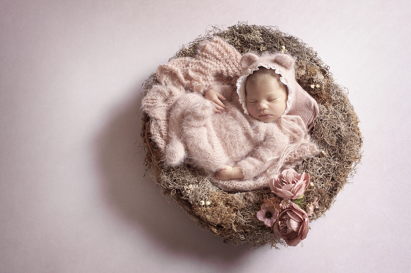 Newborn baby girl sleeping in nest with flowers wearing pink mohair romper and matching wrap and lace mohair bear bonnet