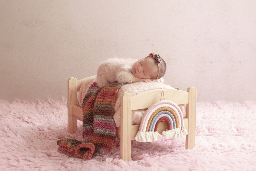 Newborn baby girl sleeping on wooden bed with pink blanket and romper and rainbow knit layer and rainbow prop on pink fur with rainbow tieback