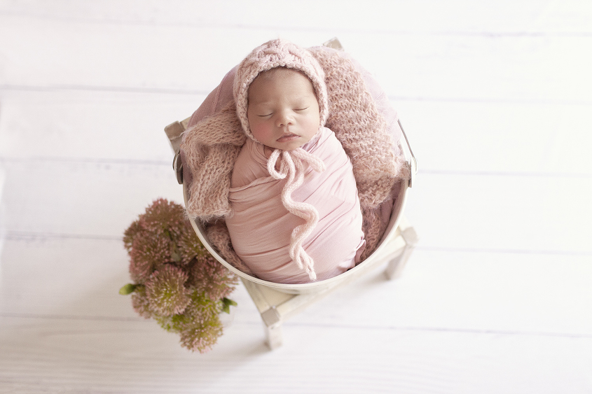 Newborn baby girl sleeping in cream bucket on white chair with pink wraps and blankets and knit bonnet with flowers in vase on white wooden floor