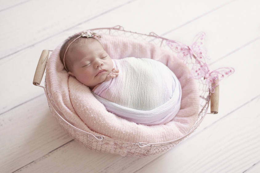 Newborn baby sleeping in pink farmers basket with pink blanket and rainbow wrap and tieback with two pink butterflies on white wooden floor