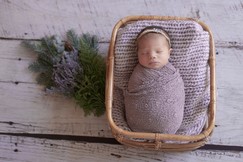 Newborn baby girl sleeping in cane basket with purple wrap and blanket and tieback with purple flowers on white wooden floor