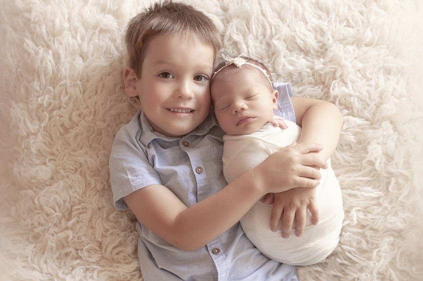 Newborn baby girl wrapped in cream wrap with cream bow tieback being held by sibling big brother wearing blue button up shirt laying on cream fur