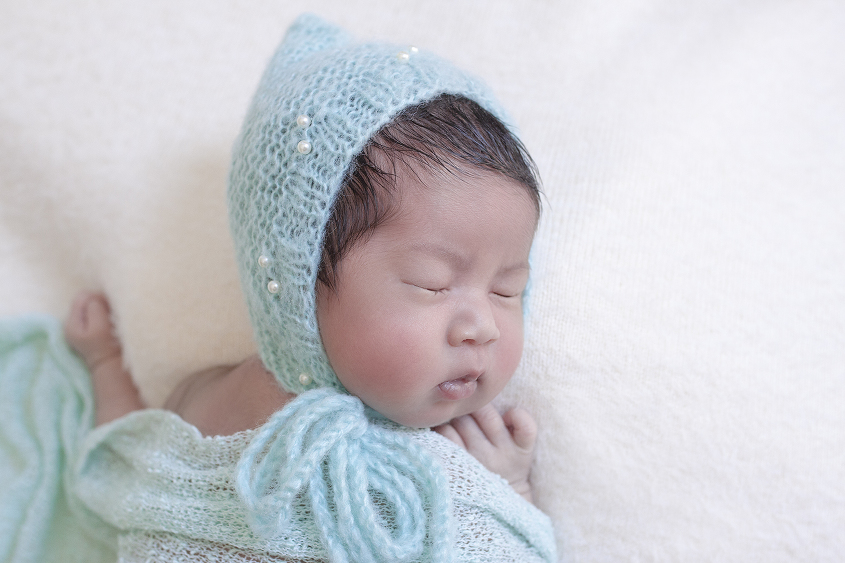 Newborn baby girl sleeping on cream blanket with mint wrap and bonnet