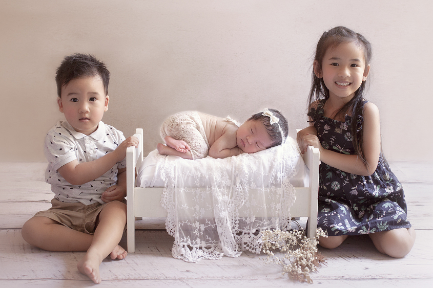 Sleeping newborn baby girl on white wooden bed wearing lace romper and lace tieback with lace wrap and sibling big sister and brother sitting beside her