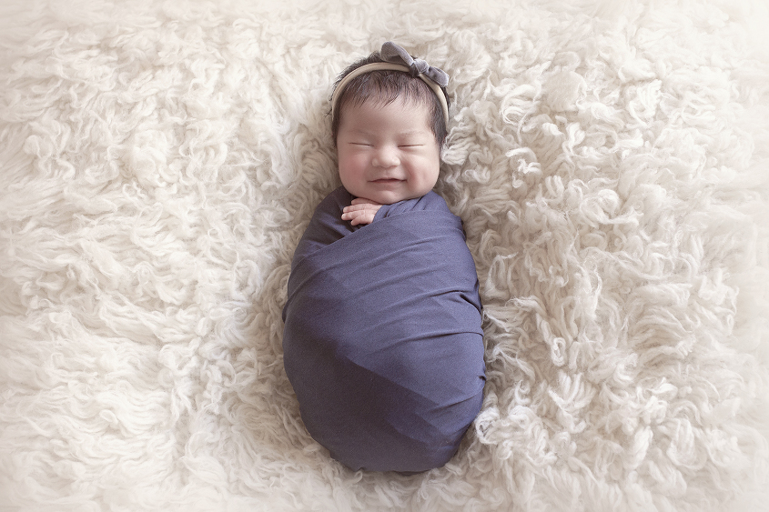 Newborn baby girl sleeping on cream fur wrapped in blue wrap with blue bow headband smiling
