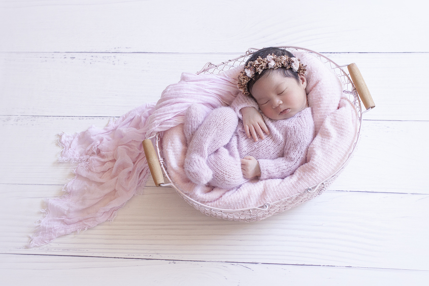 Newborn baby girl sleeping in pink farmers basket wearing pink knit romper on white wooden floor with pink floral crown