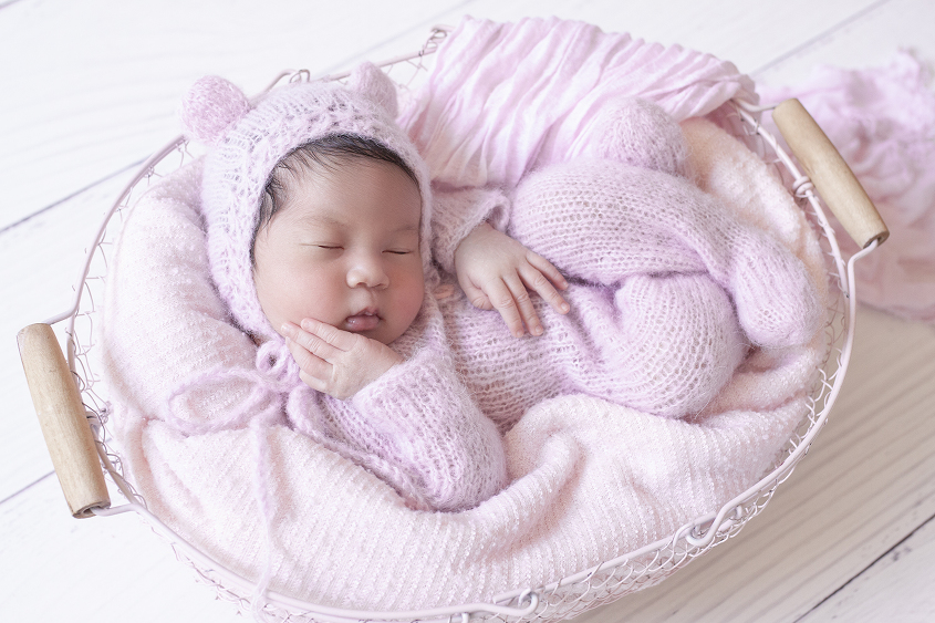 Newborn baby girl sleeping in pink farmers basket wearing pink knit romper on white wooden floor with pink knit bear bonnet