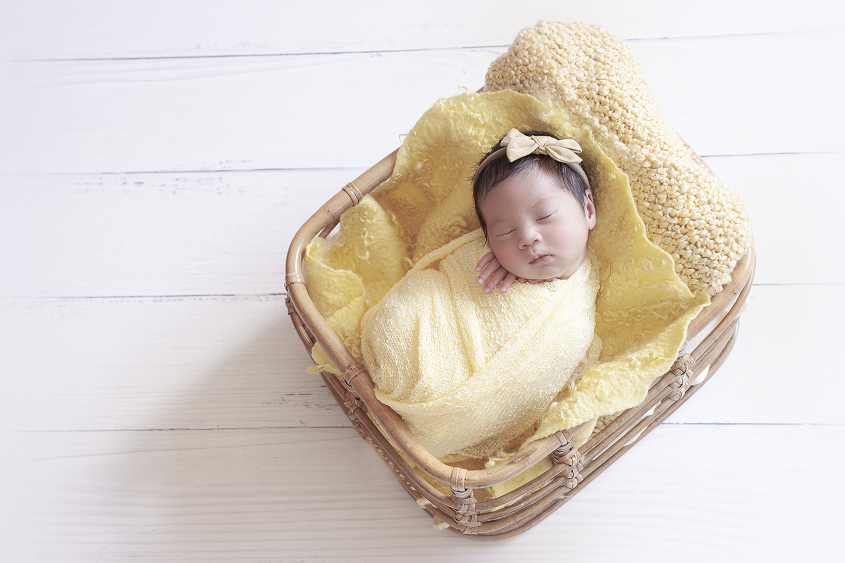 Newborn baby girl sleeping in cane basket with yellow wrap and blankets and bow on white wooden floor