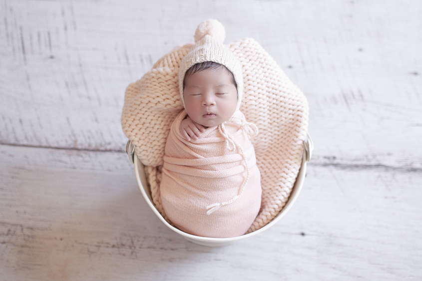 Newborn baby girl sleeping in cream bonnet wrapped in peach wrap and peack knit layer and peach knit bonnet on white wooden floor