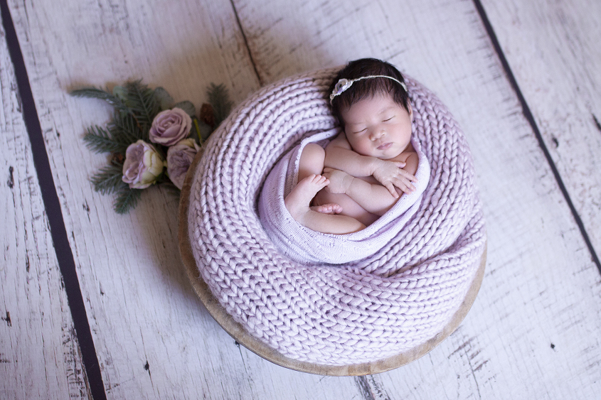 Newborn baby girl sleeping in round wooden bowl with purple knit blanket and wrap and flowers and tieback