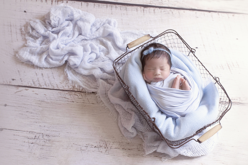 Newborn baby girl sleeping in farmers basket with blue wrap and blanket on white wooden floor