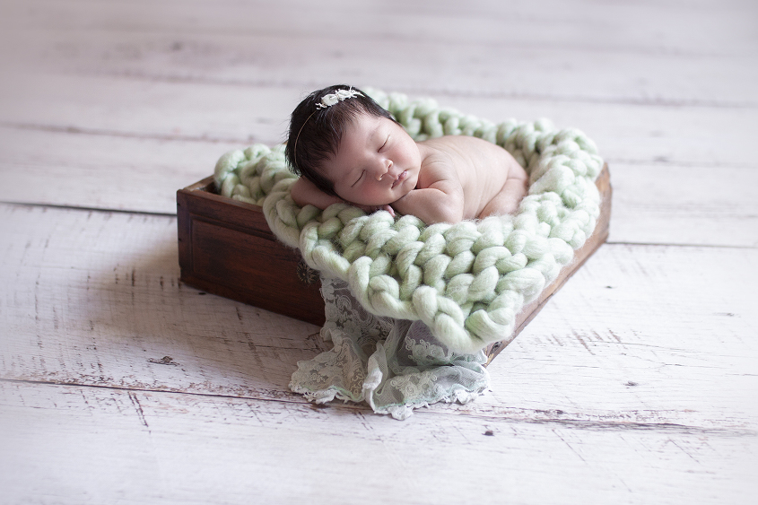 Newborn baby girl sleeping in wooden drawer with green knit layer and green lace wrap and bow headband
