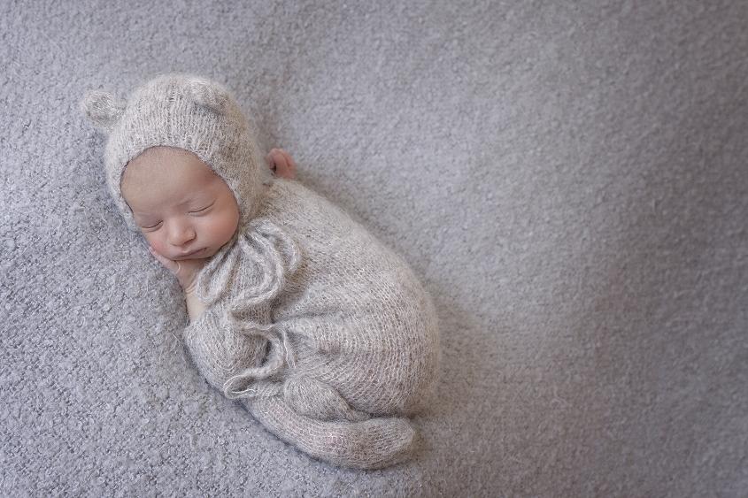 Newborn baby boy sleeping on grey blanket wearing grey knit romper and bear knit bonnet