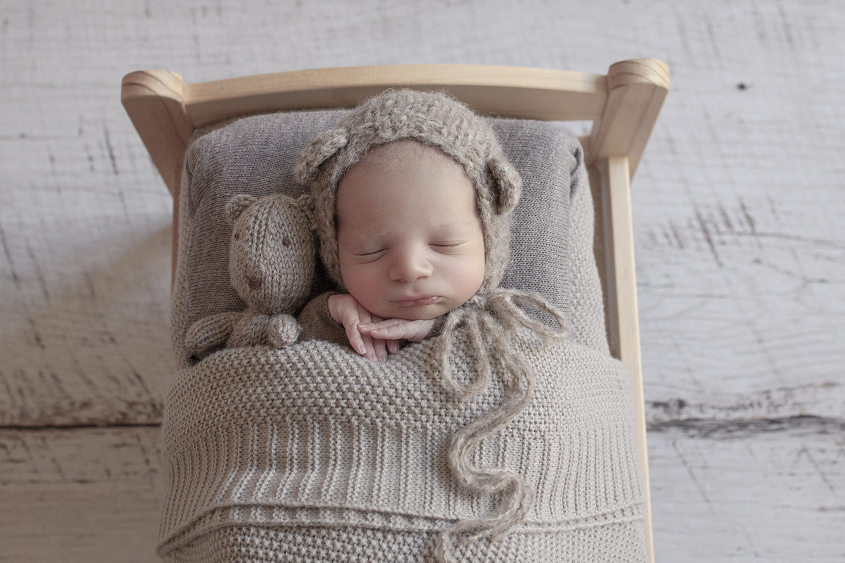 Newborn baby boy sleeping in wooden bed with brown blanket and brown knit bear bonnet and bear on white wooden floor