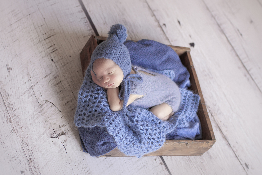 Newborn baby boy sleeping in wooden drawer wearing blue knit romper with blue blanket and knit layer on white wooden floor