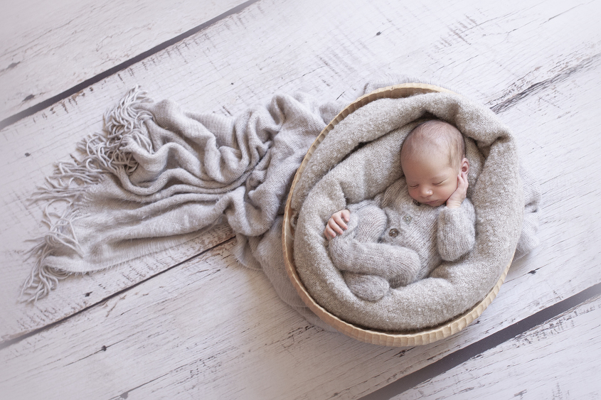 Newborn baby boy sleeping wearing grey knit romper in wooden bowl with grey blanket on white wooden floor