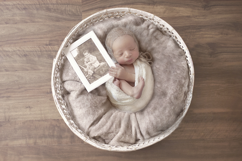 Newborn baby boy wrapped in cream wrap in white cane basket with brown felt on wooden floor holding photo of big brother who died