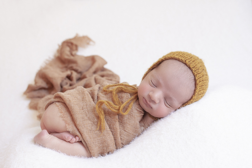 Newborn baby boy sleeping on cream blanket with mustard wrap and knit bonnet