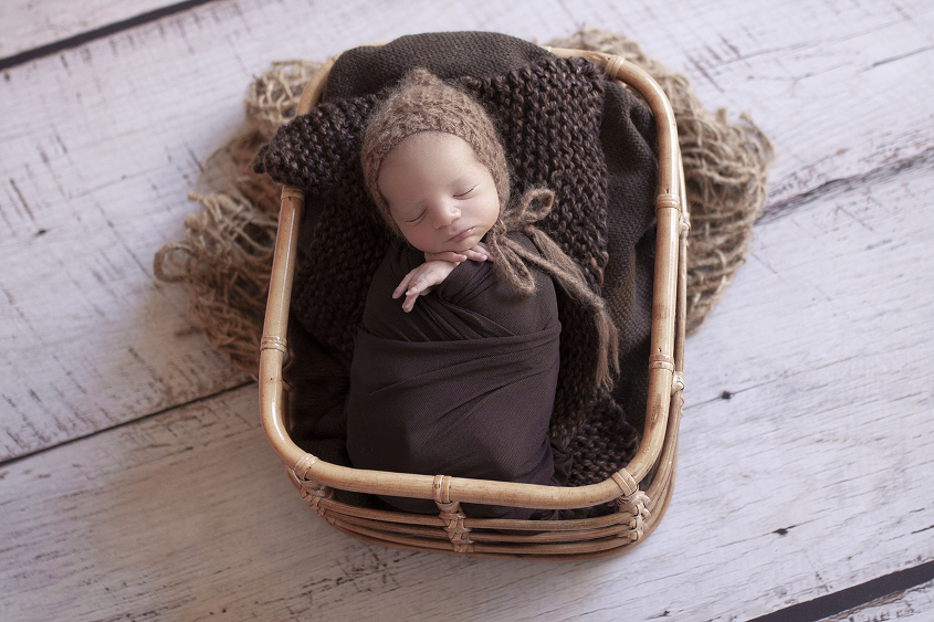 Newborn baby boy sleeping in cane basket wrapped in brown blanket with brown knit layer and bonnet and hessian layer on white wooden floor