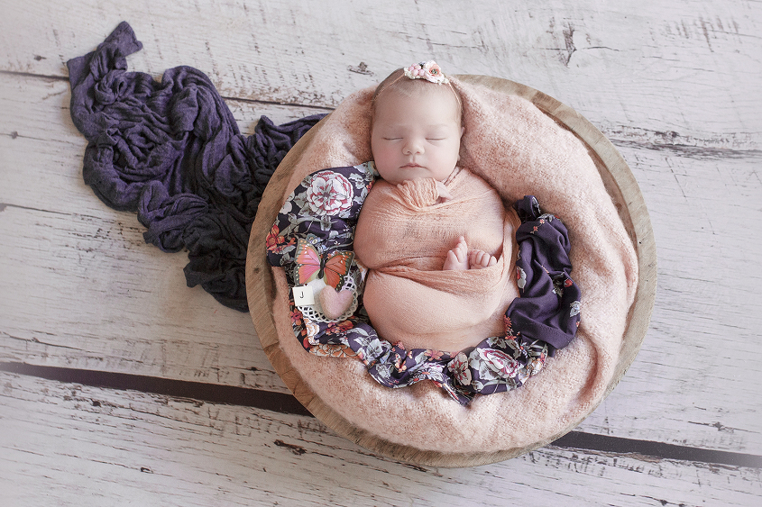 Newborn baby girl sleeping in round wooden bowl with apricot blanket and wrao laying on purple floral shirt with purple wrap on white wooden floor