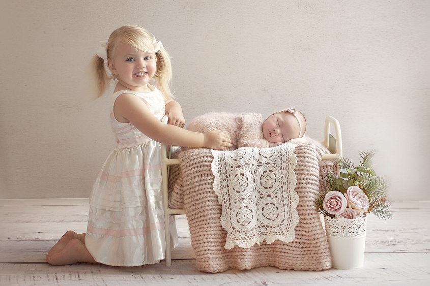 Newborn baby girl sleeping in cream iron bed with pink knit blanket and lace layer wearing pink knit romper and tieback with pink flowers and sibling sister sitting beside her