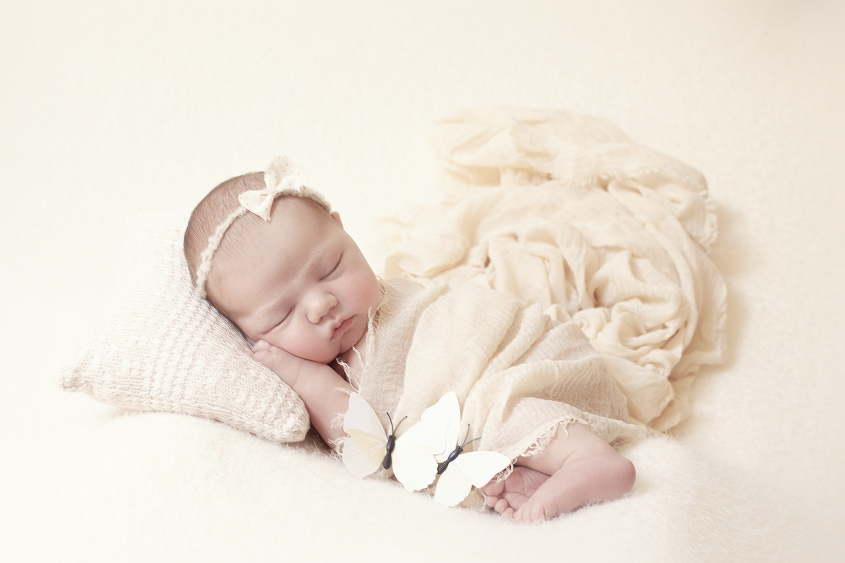 Newborn baby girl sleeping on cream blanket with cream wrap and pillow and tieback and two cream butterflies