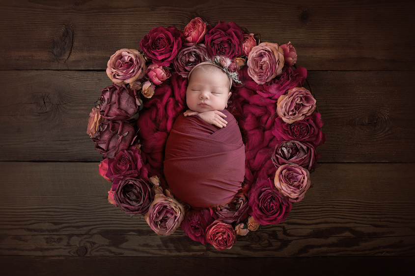Newborn baby girl wrapped in plum wrap in pink and purple flower nest on brown wooden floor