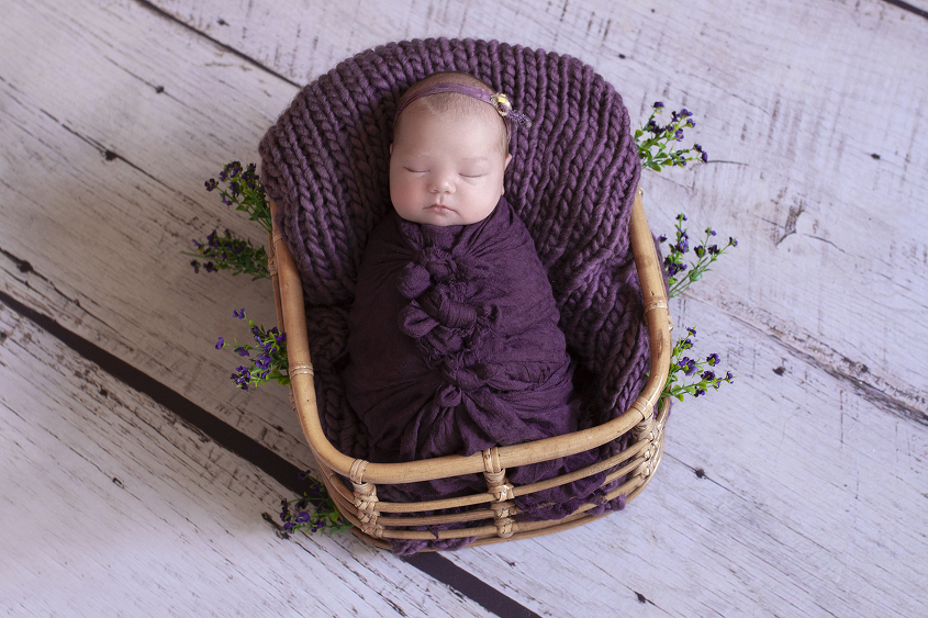 Newborn baby girl sleeping in cane basket with purple blanket and wrap and tieback and flowers on white wooden floor