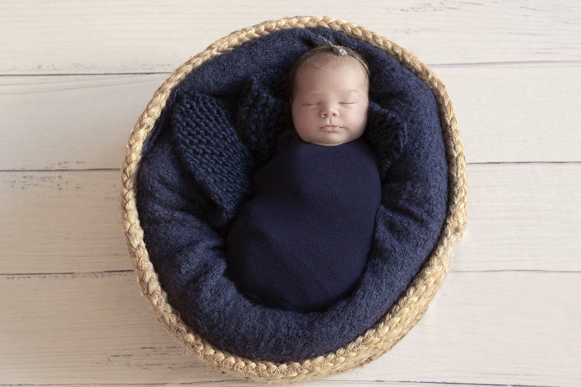 Newborn baby girl sleeping in round cane basket with navy blanket and wrap and tieback on white wooden floor
