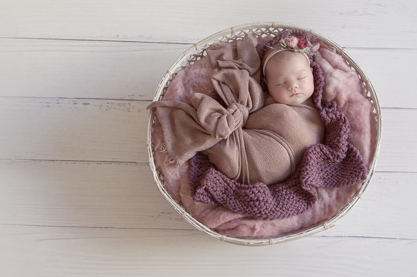 Newborn baby girl sleeping in round cane white basket with pink felt and wrap and purple knit layer and floral tieback