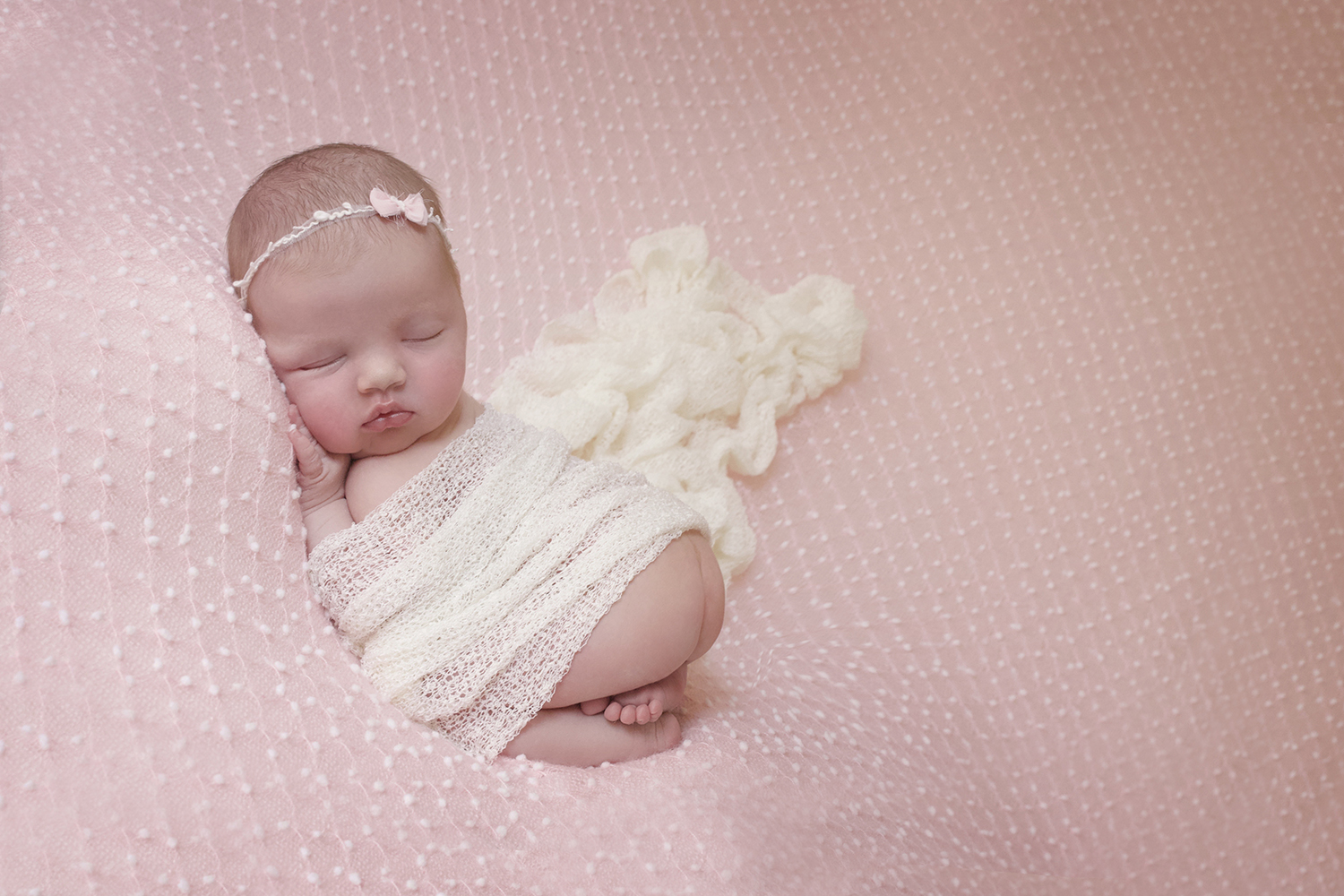Newborn baby girl sleeping on pink spotted blanket with pink bow and white wrap being supported by female photographer wearing black tshirt and leggings
