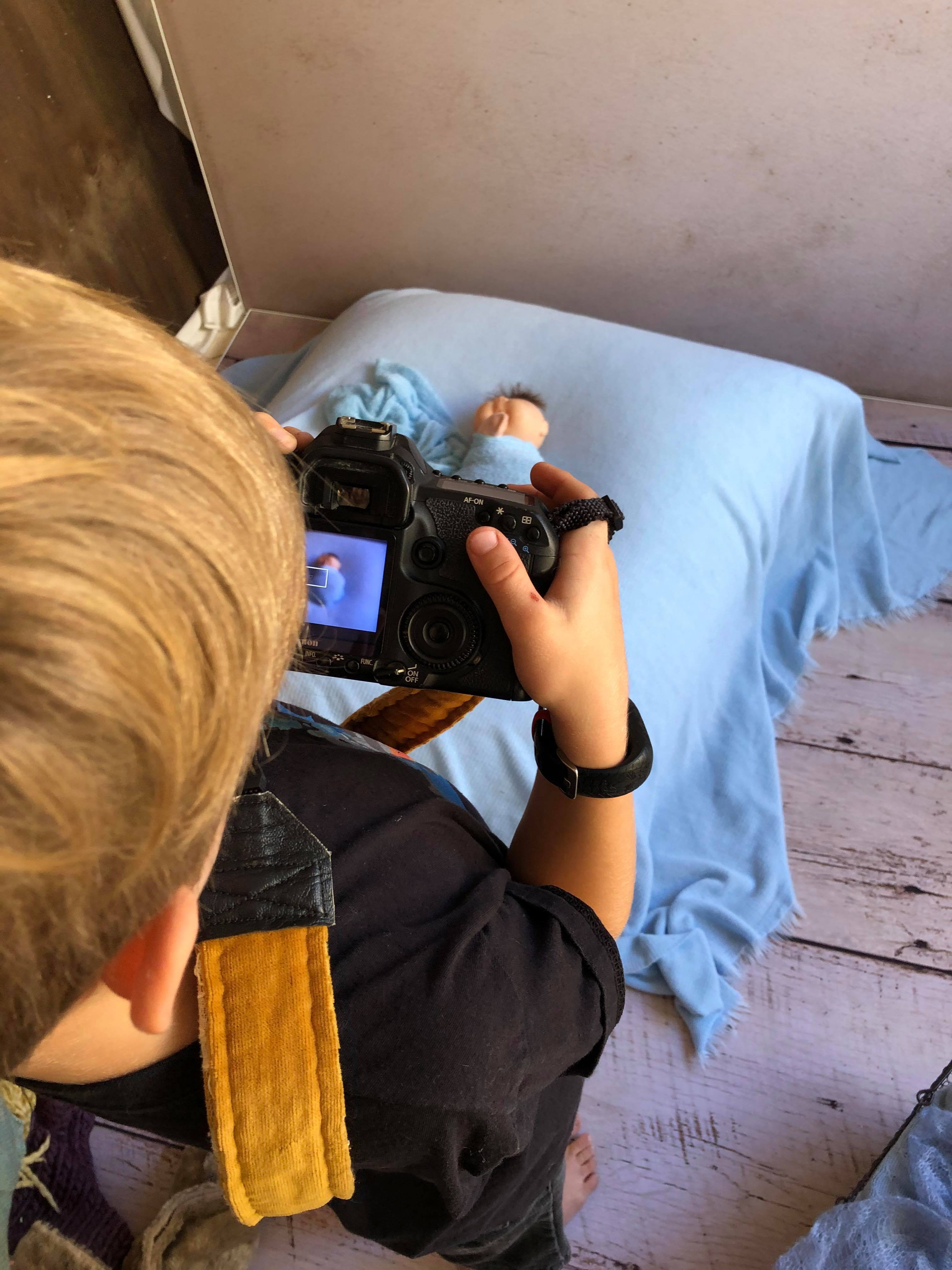 Seven year old boy taking photographs with a digital slr camera of a doll sleeping on a beanbag with blue blanket and wrap in a newborn studio