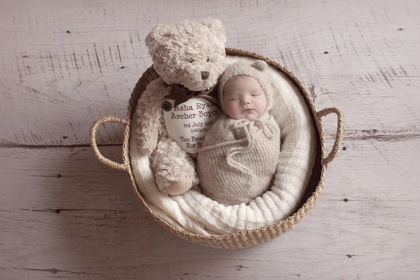 Newborn baby boy sleeping in cane basket wrapped in cream knit wrap with cream knit bear bonnet sleeping beside teddy bear holding siblings ashes on white wooden floor